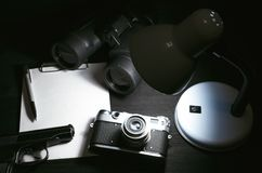 Detective. Blank page, pen, film photo camera, handgun and a binoculars on a black detective agent table background. Top view photo. Top Secret document mock up stock image