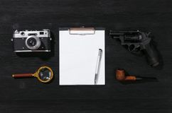 Detective. Blank page, pen, film photo camera, magnifying glass, handgun and smoking pipe on a black detective agent table background. Secret document mockup royalty free stock images
