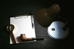 Detective. Blank top secret information paper page with copy space, magnifying glass and a smoking pipe on the detective agent table background. Espionage stock images