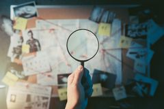 Detective board filled with evidence. Detective hand holding a magnifying glass in front of a board with evidence, crime scene photos and map. high contrast stock photo
