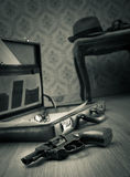 Detective briefcase on the floor. Detective open briefcase with vintage gun on the floor and borsalino hat on background stock images
