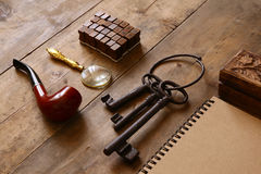 Detective concept. Private Detective tools: magnifier glass, old keys, smoking pipe, notebook. top view. vintage filtered image Stock Photography
