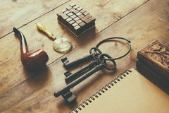 Detective concept. Private Detective tools: magnifier glass, old keys, smoking pipe, notebook. top view. vintage filtered image.  Royalty Free Stock Photo