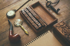 Detective concept. Private Detective tools: magnifier glass, old keys, smoking pipe, notebook. top view. vintage filtered image.  Stock Photo