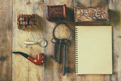 Detective concept. Private Detective tools: magnifier glass, old keys, smoking pipe, notebook. top view. vintage filtered image.  Royalty Free Stock Images