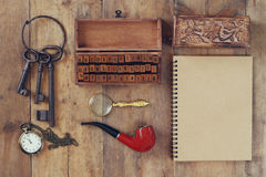 Detective concept. Private Detective tools: magnifier glass, old keys, smoking pipe, notebook. top view. vintage filtered image Stock Photo