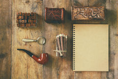 Detective concept. Private Detective tools: magnifier glass, old keys, smoking pipe, notebook. top view. vintage filtered image.  Royalty Free Stock Photos