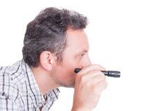 Detective of criminoloog die gebruikend klein flitslicht inspecteren Stock Foto