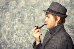 Detective. Handsome young man wearing classic hat and a coat smokes a pipe. Beauty, fashion. Side view royalty free stock photos