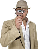 Detective holding magnifier Royalty Free Stock Images