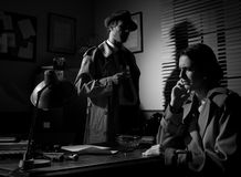 Detective interviewing a young pensive woman in his office royalty free stock photo