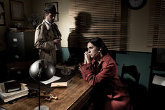Detective interviewing a young pensive woman in his office. Detective interviewing a young sad women in his office, film noir scene stock photos