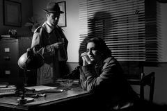 Detective interviewing a young pensive woman in his office stock photos