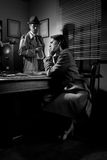 Detective interviewing a young pensive woman in his office Royalty Free Stock Image
