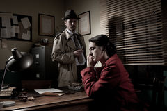 Detective interviewing a young pensive woman in his office stock photography