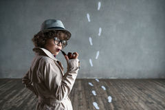 Detective. Little child with a pipe in studio royalty free stock photo