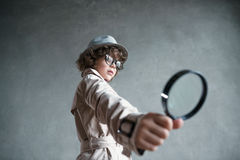 Detective. Little detective with a magnifying glass stock photo