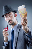 Detective looking at fake money. On the dark stock photo