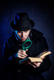 Detective with magnifier glass and book Stock Photography