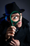 Detective with magnifier glass Stock Images