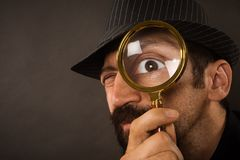 Detective with magnifying glass. The curious detective is looking with magnifier or magnifying glass or loupe on dark gray background, detective service concept royalty free stock photo