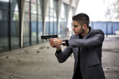 Detective or mobster or policeman aiming a firearm. Well dressed handsome young detective or policeman or mobster standing in an urban environment aiming a royalty free stock images