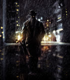 Detective. Noir detective walking a night city lights Stock Image