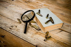 Detective novel. Concept with book, bullets and magnyfying glass stock photography