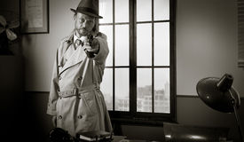 Detective pointing a gun Stock Photography
