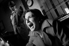 Detective pointing a gun to a terrified woman Royalty Free Stock Photos