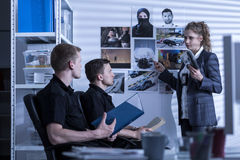 Detective and police officers. Are looking at photos Royalty Free Stock Images