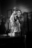 Detective protecting a young woman pointing a gun. Brave detective pointing a gun and young scared women hiding behind him, 1950s film noir style stock photography