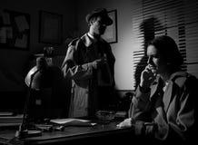 Detective que se entrevista con a una mujer pensativa joven en su oficina Foto de archivo libre de regalías