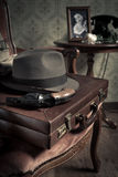 Detective ready to go. Detective equipment with briefcase, hat and gun, vintage interior on background stock image