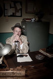 Detective smoking at desk Stock Photography