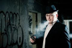 Detective smoking with gun Royalty Free Stock Photos