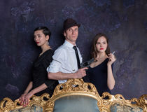 Detective story studio shot. Man and two women. Agent 007. A man in a hat with a pistol and two women in black Stock Photos