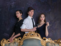 Detective story studio shot. Man and two women. Agent 007. A man in a hat with a pistol and two women in black Stock Images