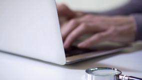 Detective typing information about investigation, magnifying glass on backround royalty free stock photography
