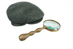 Detective Warm Cap and Vintage Magnifying Glass Royalty Free Stock Photos