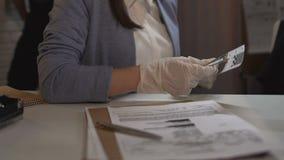 Detectivearbeider die kogelgrootte meten en gegevens in het rapport van de misdaadscène ingaan stock video