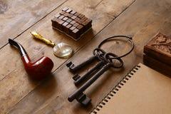 Detectiveconcept Privé-detectivehulpmiddelen: meer magnifier glas, oude sleutels, rokende pijp, notitieboekje Hoogste mening wijn Stock Fotografie