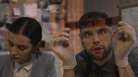 Detectives que analizan las fotos de la película para atar en caso de que informe, prueba de las pruebas almacen de video