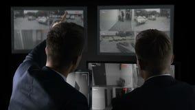 Detectives que miran los expedientes de la cámara, buscando para las pruebas del crimen, investigación almacen de metraje de vídeo