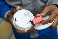Detector de humo de Removing Battery From del electricista Foto de archivo libre de regalías