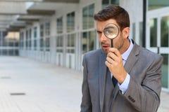 Detektiv, der durch eine Lupe schaut lizenzfreies stockfoto
