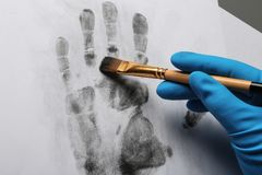 Detektiv, der Fingerabdrücke mit Bürste vom Papier auf Grau nimmt lizenzfreie stockfotografie