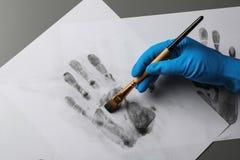 Detektiv, der Fingerabdrücke mit Bürste vom Papier auf grauem Hintergrund, Draufsicht nimmt stockfotografie