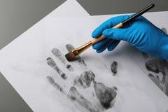Detektiv, der Fingerabdrücke mit Bürste vom Papier auf grauer, Draufsicht nimmt VERBRECHENSERMITTLUNG lizenzfreie stockbilder