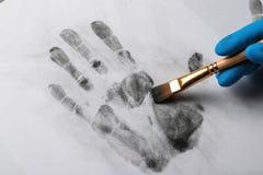 Detektiv, der Fingerabdrücke mit Bürste vom Papier, Nahaufnahme nimmt lizenzfreie stockfotografie